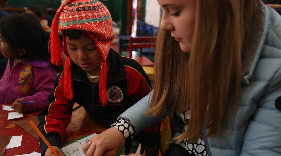 Adolescente ayudando a un niño durante una sesión de manualidades como parte de su voluntariado para jóvenes.